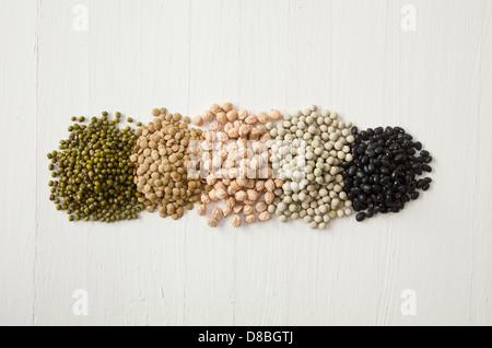 Des tas de pois, haricots, lentilles, les germes et les légumineuses dans une ligne sur une surface en bois rustique. Banque D'Images
