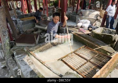 En remuant la pâte de bois dans le processus de fabrication du papier traditionnel dans Xiaotunxiang, Guizhou Banque D'Images