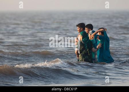 Famille sur une plage à Mumbai, Inde Banque D'Images