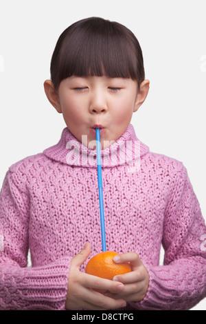 Portrait de jeune fille boire une orange avec une paille, studio shot Banque D'Images