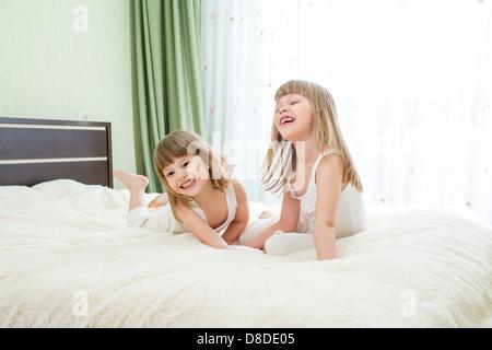 Deux petites filles lying on bed Banque D'Images