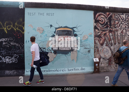 Mur de Berlin East Side Gallery peinture de voiture Trabant briser mur avec man walking passé, retour à Berlin Allemagne Banque D'Images