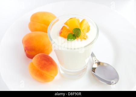 Yaourt frais aux abricots (fruits) dans bécher en verre blanc, gros plan sur la plaque horizontale, copy space Banque D'Images