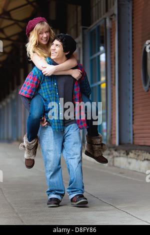 Jeune homme donnant à une jeune femme un piggyback ride Banque D'Images