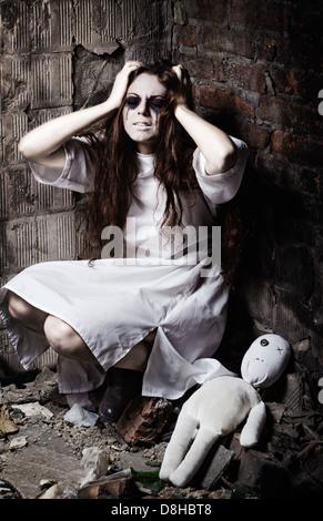 Style d'horreur tourné: l'étrange fou fille et sa poupée moppet Banque D'Images