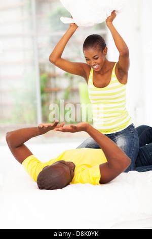 Jeune couple africain ludique guerre d'oreillers dans la chambre Banque D'Images
