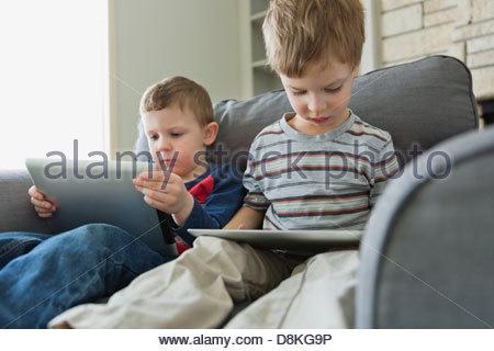Les garçons sur canapé jouant avec les tablettes numériques Banque D'Images