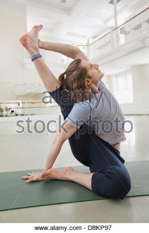 Man practicing yoga in yoga studio Banque D'Images