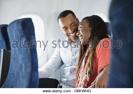 Smiling couple snuggling in airplane Banque D'Images