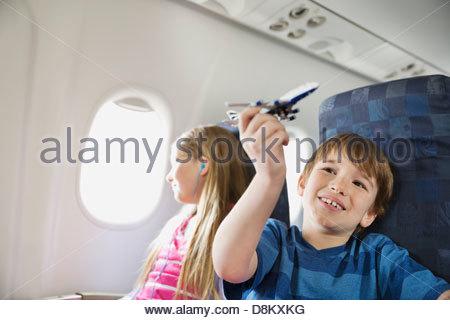 Boy Playing with toy avion tandis que sœur écoute de la musique en avion Banque D'Images