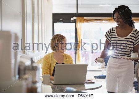 Serveuse qui sert du café à la femme du coffee shop Banque D'Images