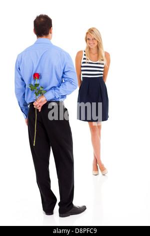 Jeune homme romantique rose se cacher derrière son dos Banque D'Images