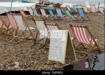 Transats inoccupés et avis à l'état humide journée d'été à la plage de la bière dans le Devon Banque D'Images