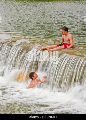 Deux petits garçons dans la rivière Blanco, Texas TX Banque D'Images