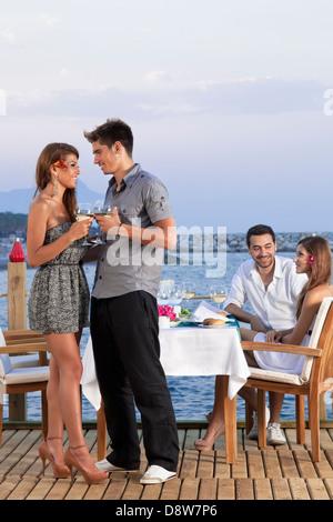 Jeune couple romantique sur une terrasse en bois donnant sur la mer de boire du vin blanc. Banque D'Images