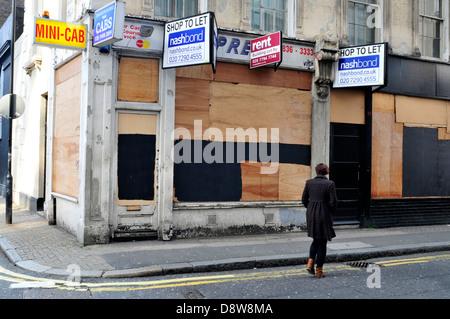 Une femme passe devant une boutique à bord jusqu'au centre de Londres, au Royaume-Uni. Banque D'Images