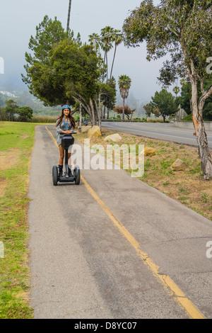 Une adolescente, dans un casque, monte sur un deux-roues transporteur personnel Segway sur une piste cyclable à Banque D'Images