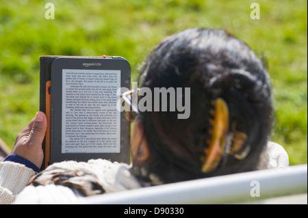 Femme lisant Amazon Kindle livre dehors à Hay Festival 2013 Hay-on-Wye Powys Pays de Galles UK Banque D'Images