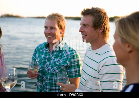 Trois personnes rire et boire, Fejan, archipel de Stockholm, Suède.