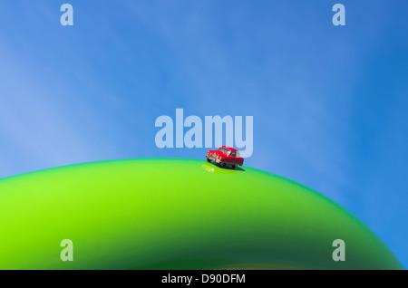 Petite voiture jouet rouge reposant sur un grand anneau vert contre le ciel bleu Banque D'Images
