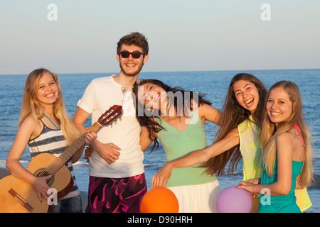 Groupe de jeunes bénéficiant d'beach party avec la guitare et des ballons Banque D'Images