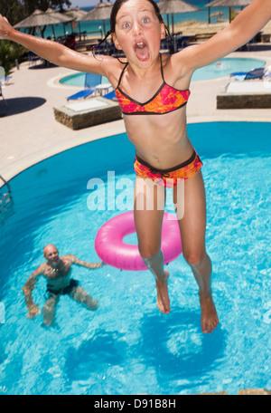 Une fille de sauter dans la piscine, la Grèce. Banque D'Images