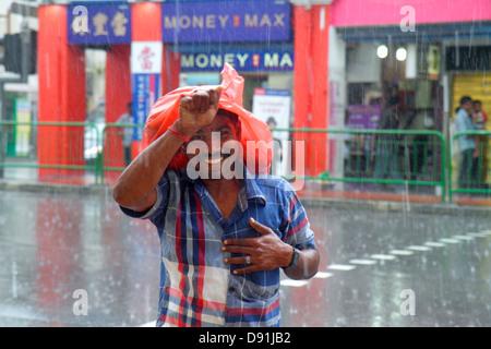 Little India de Singapour Serangoon Road running homme asiatique pluie pluie de mousson climat météo plus de couvre Banque D'Images