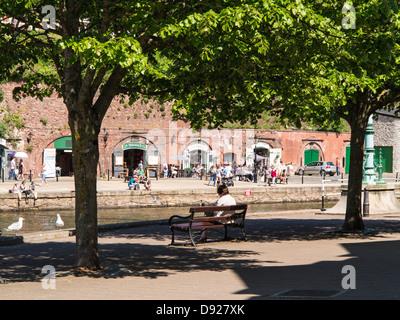 Femme assise sur un banc à l'ombre à côté de la rivière exe au quai d'Exeter, Devon, Angleterre