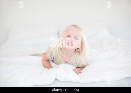 Little girl lying on bed Banque D'Images