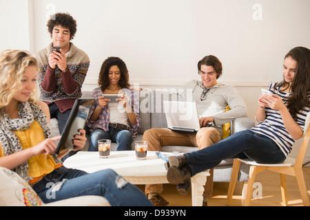 Des amis à l'aide de la technologie dans la salle de séjour Banque D'Images