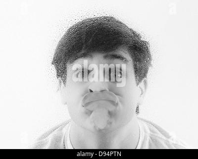 Close-up of adolescent avec visage appuyé contre le verre humide Banque D'Images