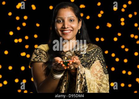 Portrait de femme tenant une diya et souriant en face de Diwali decoration Banque D'Images