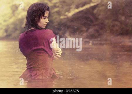 Woman in dress debout dans l'eau recouverte de brouillard Banque D'Images