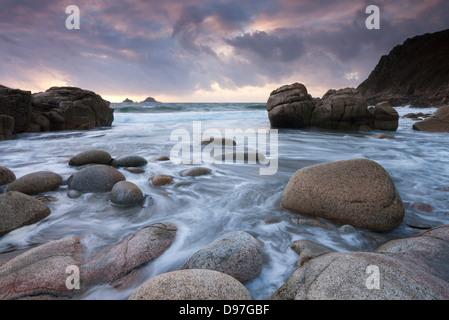 Coucher du soleil sur les rives rocheuses Porth Nanven, près de St Just, Cornwall, Angleterre. Banque D'Images