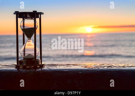 Sablier ou horloge de sable en face d'un beau clair lever ou le coucher du soleil. Banque D'Images