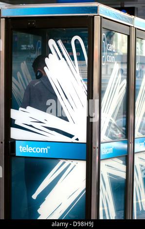L'homme parle dans une rue Telecom téléphone payphone booth, Nouvelle-Zélande Banque D'Images