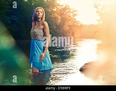Femme en robe bleue walking in river pendant le coucher du soleil Banque D'Images