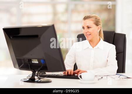 Middle aged female office worker working on computer Banque D'Images