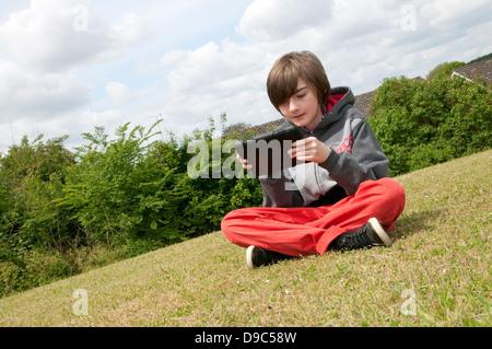 Jeune homme garçon à l'aide d'ipad mini tablet computer Banque D'Images