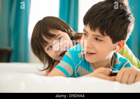 Girl boy listening to mp3 player on bed Banque D'Images