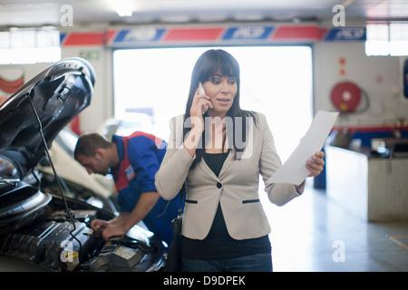 Malheureuse femme lecture document relatif à sa voiture Banque D'Images