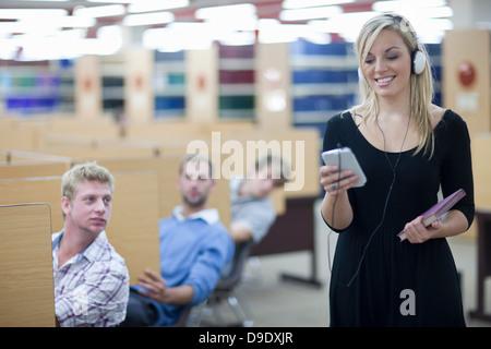 Trois étudiants hommes regardant étudiante Banque D'Images
