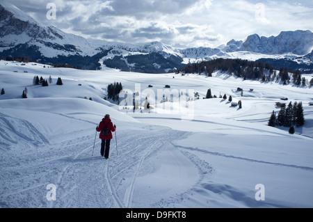 Une femme marche sur un sentier de neige à l'Alpe di Siusi Ski près de la ville d'Otisei dans les Dolomites, le Banque D'Images