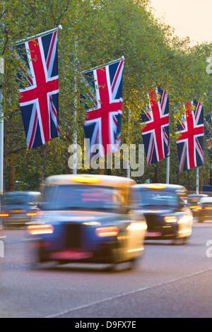 Des taxis noirs le long de la galerie marchande avec drapeaux Union Jack, London, England, UK Banque D'Images