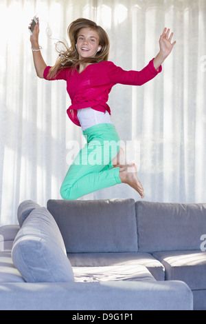 Portrait of a smiling girl jumping on a couch Banque D'Images