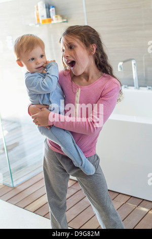 Fille portant son frère et à la surprise dans une salle de bains Banque D'Images