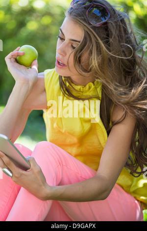 Woman holding an Apple et à la tablette numérique à un Banque D'Images