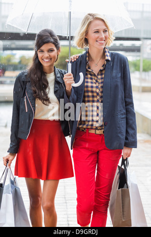 Femme amis marchant avec shopping bags and smiling Banque D'Images