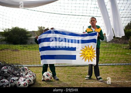 Un portrait deux jeunes enfants à l'école tenant un drapeau Uruguay H P Williams dans les écoles de football Stompneus Banque D'Images