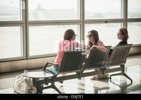Deux adolescentes et une femme assise dans la salle d'embarquement de l'aéroport Banque D'Images